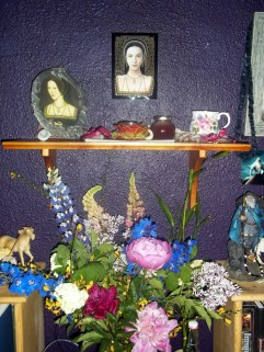 a full view of the shrine for Anne; under the rose teacup candle holder are the printed-out prayers submitted for her