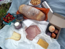 local smoked humanely raised ham, Cottwald and Mourbier cheeses, a handcrafted cherry pocket pie, local artisan bread, local strawberries, petits four, three-flower honey, champagne mustard, and rose wine disguised in a metal flask